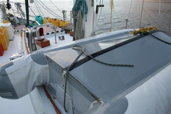 The dinghy is stored in front of the cockpit, tied down.